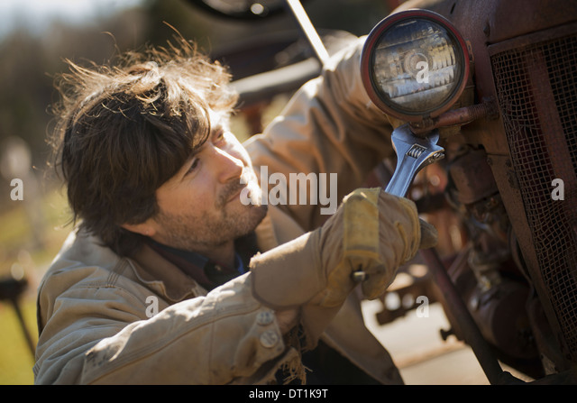 Working on an organic farm A man in a brown jacket using a spanner and working on farm machinery A tractor with - Stock Image