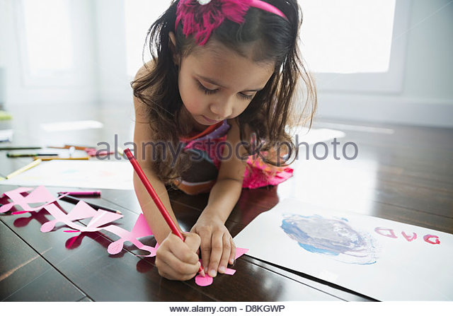 Girl making paper doll chain at home - Stock Image