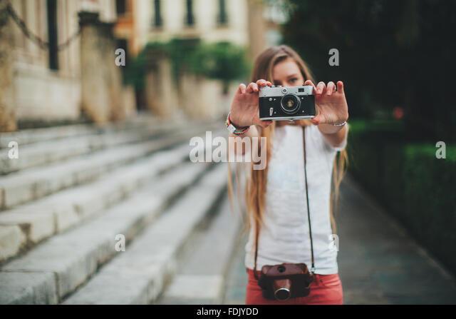 Young woman holding retro film camera, Seville, Spain - Stock-Bilder