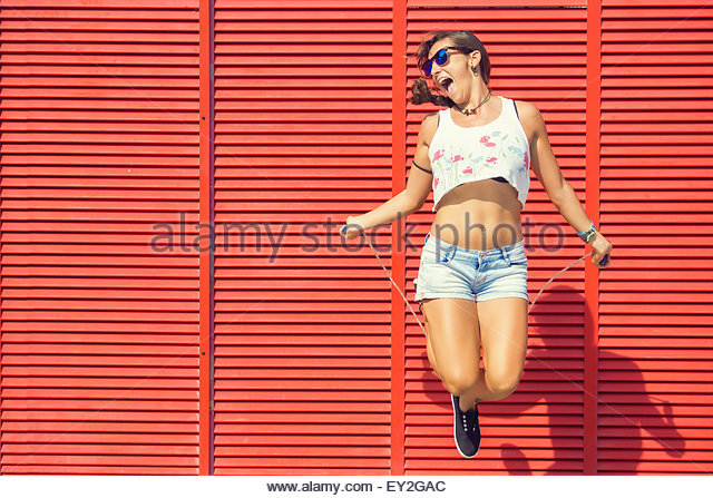 Woman jumping rope on red background - Stock-Bilder