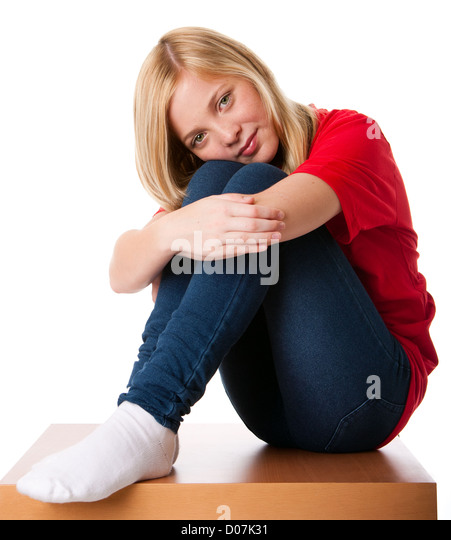 Cute teenager girl feeling lonely sitting alone with knees pulled up and arms around legs, isolated. - Stock Image