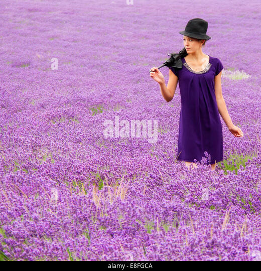 Woman with hat and umbrella standing in lavender field - Stock Image