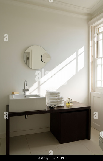 Modern bathroom with black washstand and round mirror - Stock Image