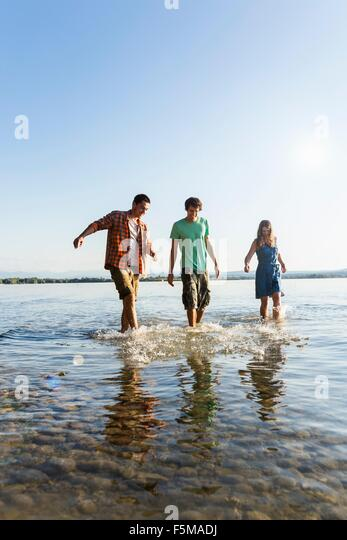 Front view of friends in a row walking ankle deep in water, Schondorf, Ammersee, Bavaria, Germany - Stock Image