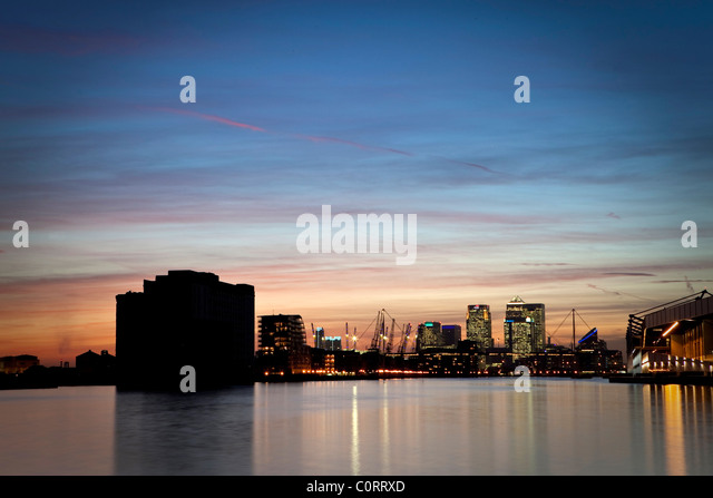 Isle of Dogs, Londons financial centre at dusk reflected in the waters of the Royal Victoria Dock - Stock Image