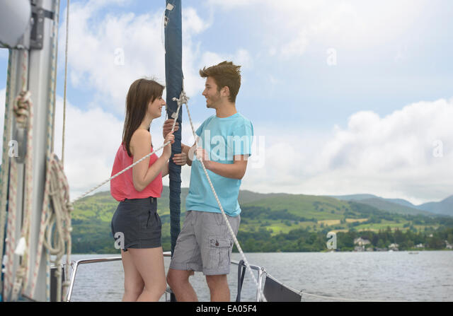 Young couple standing on bow of yacht sailing on lake under bright sunlight - Stock Image