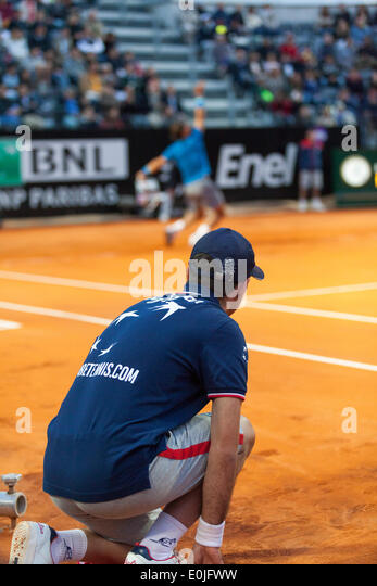 Ball boy at side of court while Rafael Nadal serves in tennis match - Stock Image