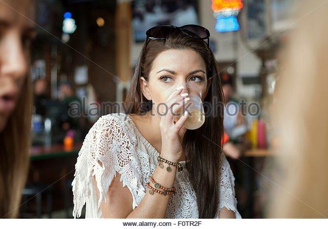 Young woman sitting in cafe with friends, drinking cool drink - Stock-Bilder