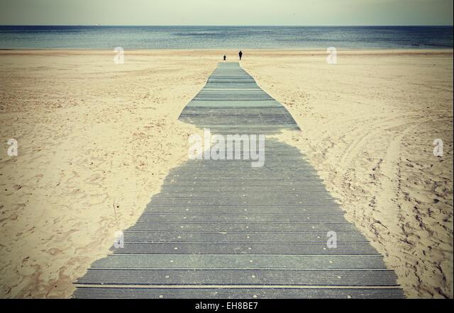 Retro toned photo of a boardwalk on beach. - Stock-Bilder