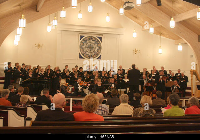 Choir and orchestra having a public performance in church - Stock Image