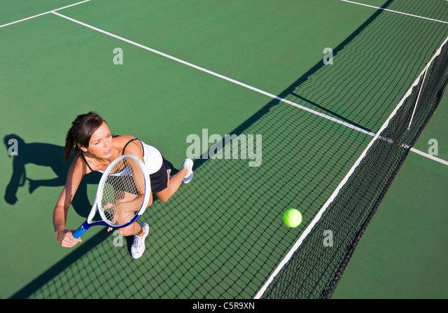 Tennis player stretches to return ball. - Stock Image