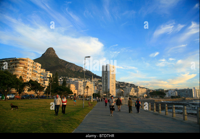 Walkers and joggers with Lions Head in back at Sea Point beachfront - Stock Image