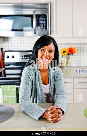 Smiling black woman in modern kitchen interior - Stock Image