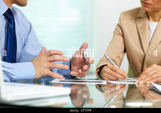 Business people sitting together holding a discussion concerning new strategic movements - Stock Image