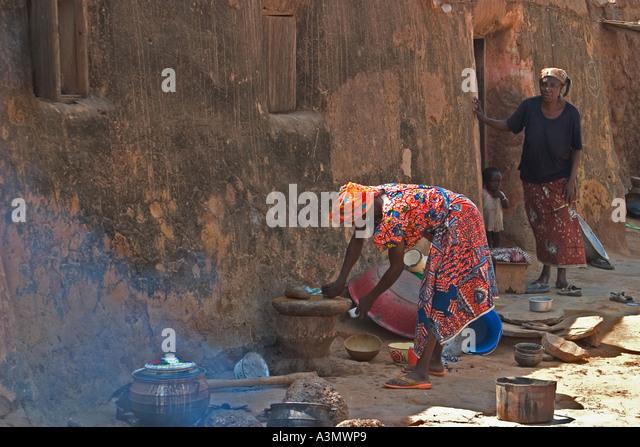 Village woman, Larabanga, Ghana, preparing food for cooking on open firehouse. - Stock Image