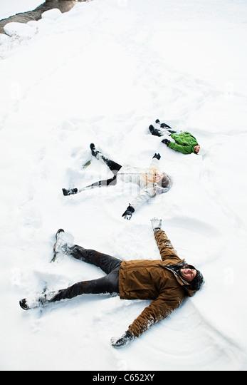 Family making snow angels - Stock-Bilder