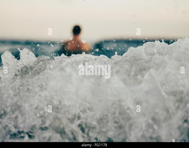Close-Up Of Wave With Blurred Man In Distance - Stock-Bilder