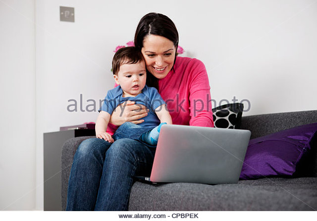 A mother and her baby son sitting on a sofa looking at a laptop - Stock-Bilder