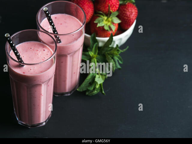 Strawberry and mint smoothie in tall glasses, bawl of fresh berries on dark rustic wood background - Stock Image