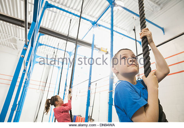 Boy climbing rope in gym - Stock Image