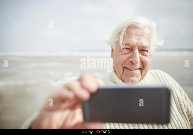 Smiling senior man taking selfie with cell phone on beach - Stock Image
