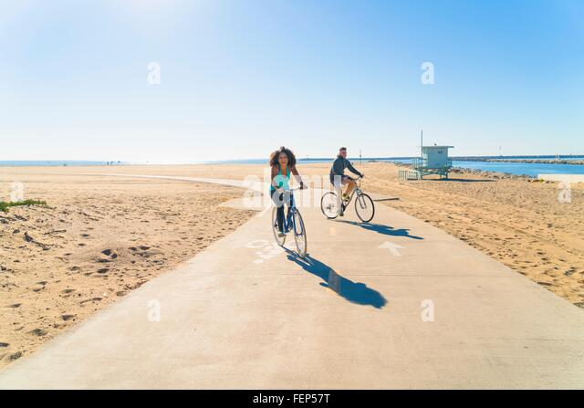 Couple cycling along pathway at beach - Stock Image