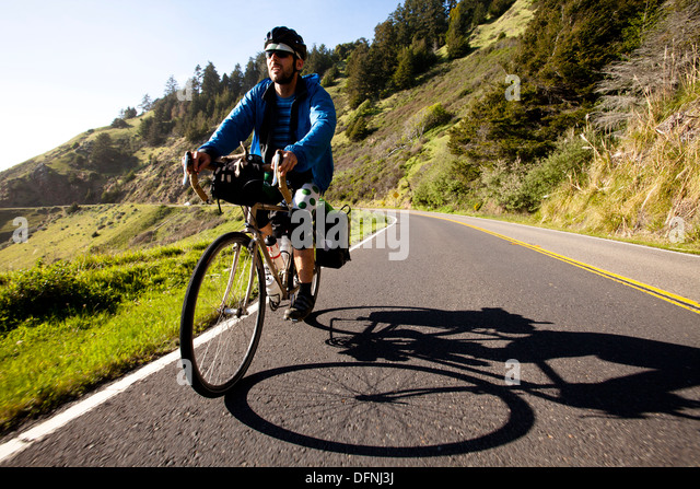A male cyclist rides his touring bike down the Pacific Coast Highway near Jenner, California. - Stock-Bilder
