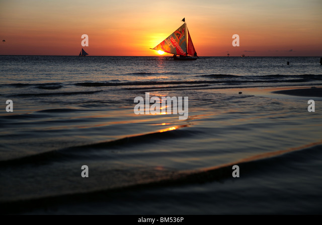 A sail boat passes the sunset on White Beach, Boracay, the most famous tourist destination in the Philippines. - Stock Image