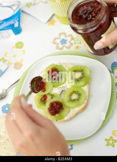Close-up of person's hand putting jam on slices of kiwi fruit - Stock Image