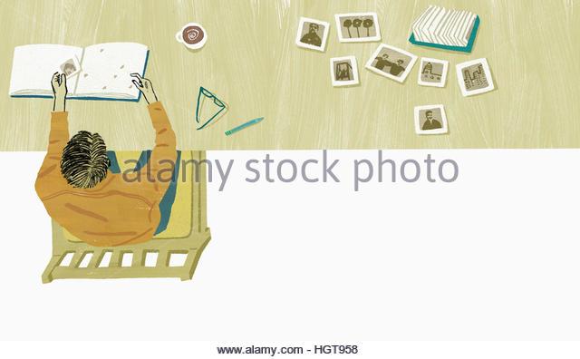 Man organizing photographs into album - Stock-Bilder