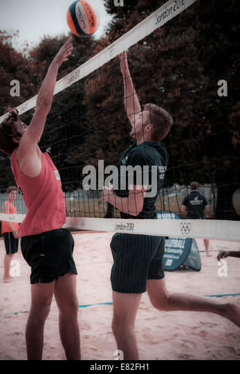 Two men playing volleyball at the net. - Stock Image