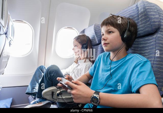 Boy using remote control to change channels on airplane - Stock-Bilder