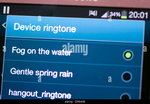 Selecting ringtone on mobile phone screen - Stock Image