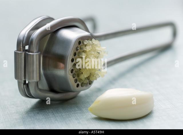 Garlic press and clove of garlic - Stock Image