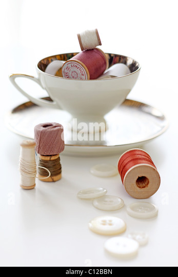 chine tea cup with spools of thread and buttons - Stock Image