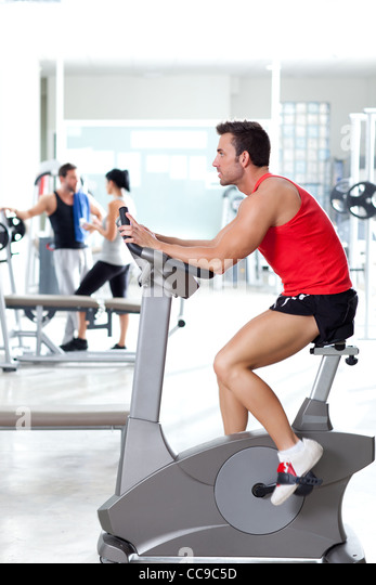 man on stationary bicycle at sport fitness gym interior - Stock Image