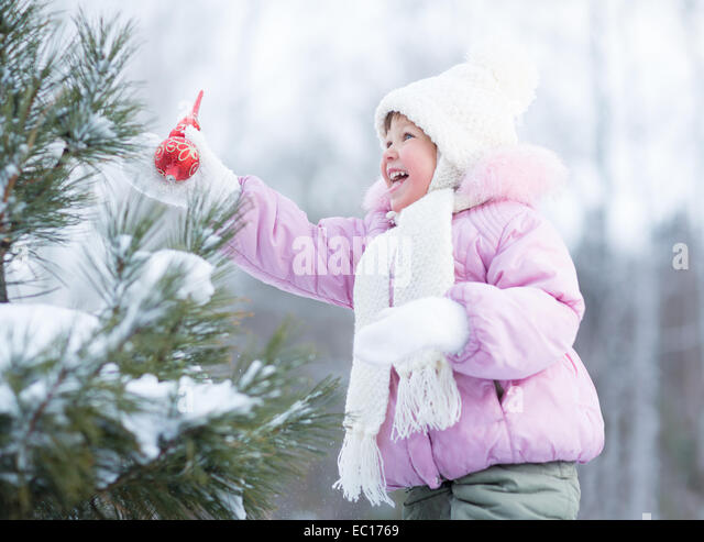 Happy kid making christmas tree decorations outdoor - Stock Image