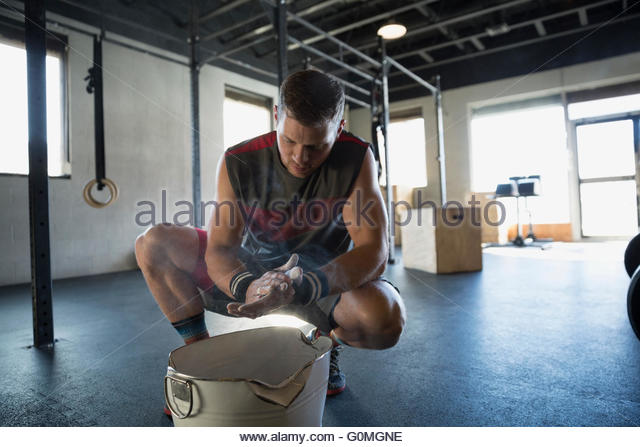 Man chalking hands before weightlifting at gym - Stock Image