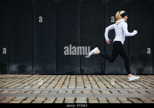 View of young woman running on sidewalk in morning. Health conscious concept with copy space. - Stock Image