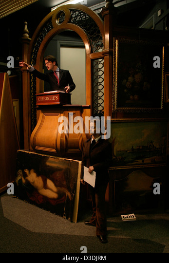 Auctioneer Will O'Reilly handles bidding at sale of ski posters at Christie's auction house, South Kensington. - Stock Image