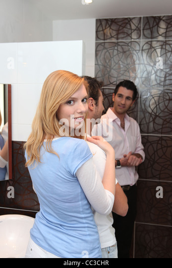 Woman hugging her boyfriend in a bathroom - Stock Image