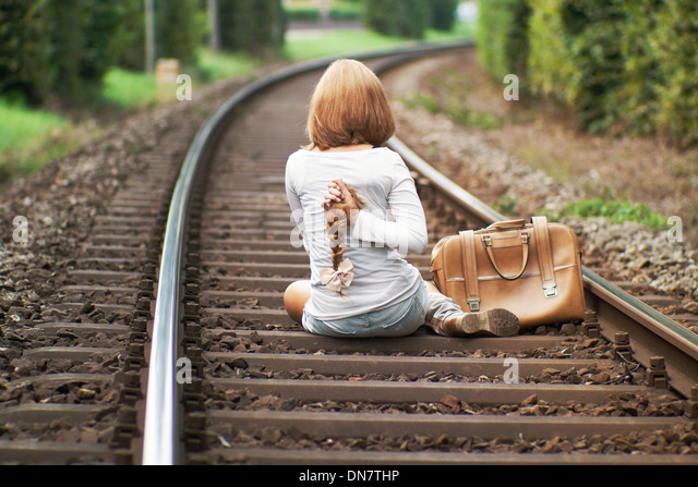 Woman sits on railway track with cut off pigtail in hand - Stock Image