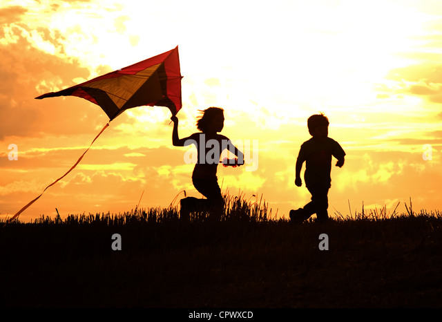 Two kids flying a kite at sunset invoke childhood memories. - Stock Image