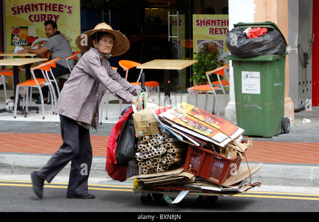 Singapore: poor woman collecting paper and kartons, pushing cart down street - Stock Image