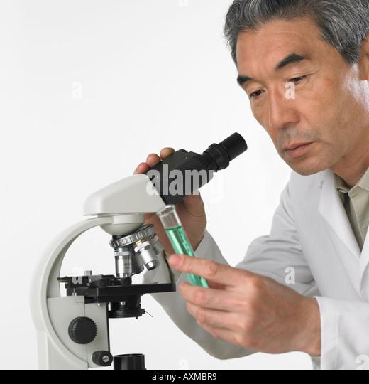 Man with vial of fluid and microscope - Stock Image