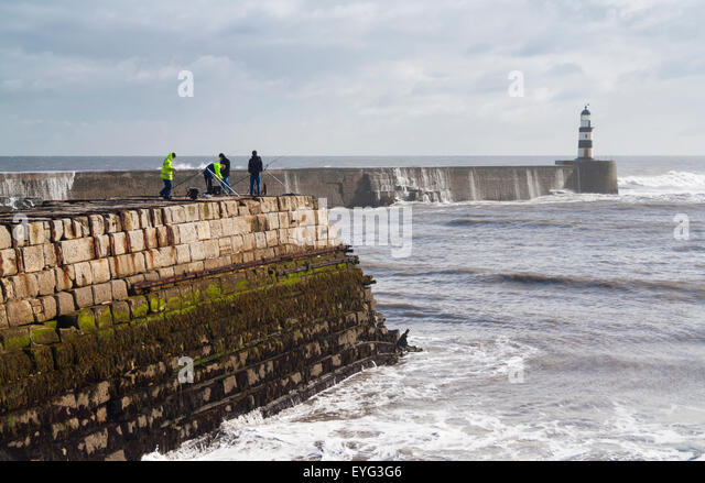 People fishing from Seaham pier on a stormy day. Seaham, County Durham, England, UK - Stock Image