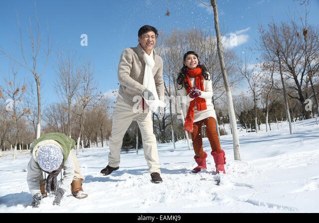 A family of three in the snow snowball fights - Stock Image