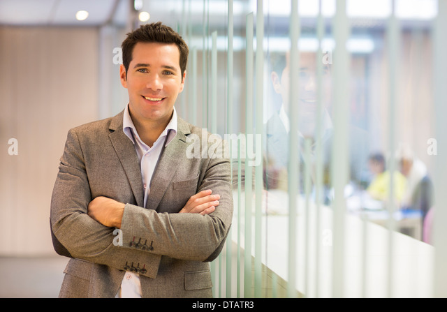 Portrait of smiling handsome businessman in office, looking camera - Stock Image