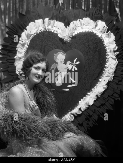 1920s 1930s SMILING YOUNG WOMAN  LOOKING AT CAMERA FINGER WAVE HAIR PEARLS FEATHER BOA GIANT VALENTINE HEART - Stock Image