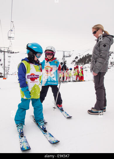 children on skis wearing ski clothes and helmets waiting with a woman for a skiing lesson at a ski school collection - Stock Image